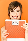 Young woman holding scale and smiling