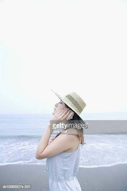 Young woman holding seashell to hear on beach, side view