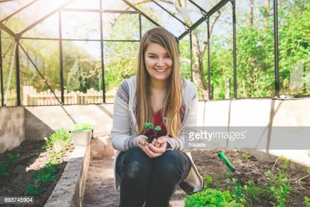 junge Frau hält Sämling kniend im Gewächshaus