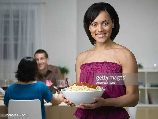 Young woman holding serving bowl of spaghetti, others at dinner table, at home