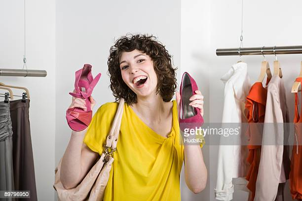 A young woman holding shoes in a store and smiling