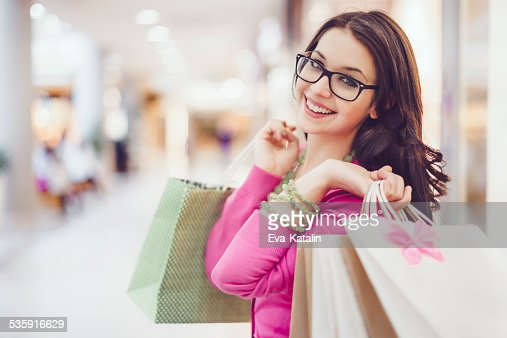 Young woman holding shopping bags in a shopping mall : Stock Photo