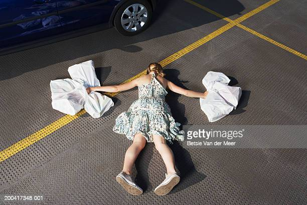 Young woman holding shopping bags in carpark, lying face down