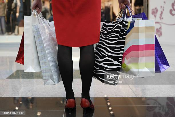 Young woman holding shopping bags, low section