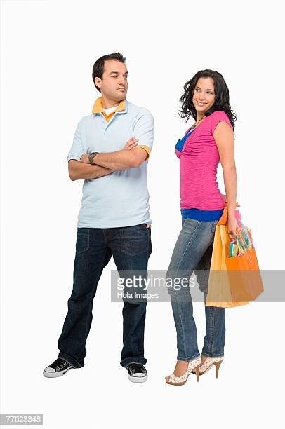 Young woman holding shopping bags with a young man standing beside her