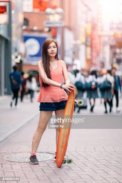 渋谷でスケート ボードを保持している若い女性