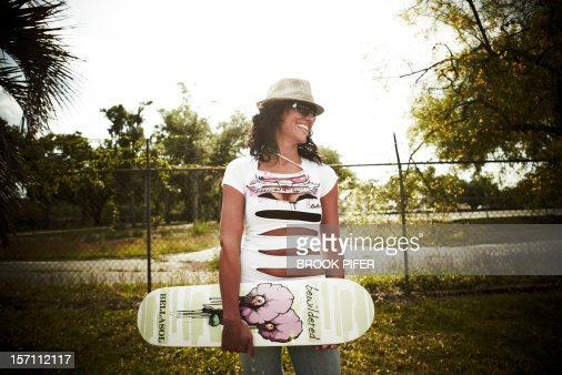 Young woman holding skateboard : Stock-Foto