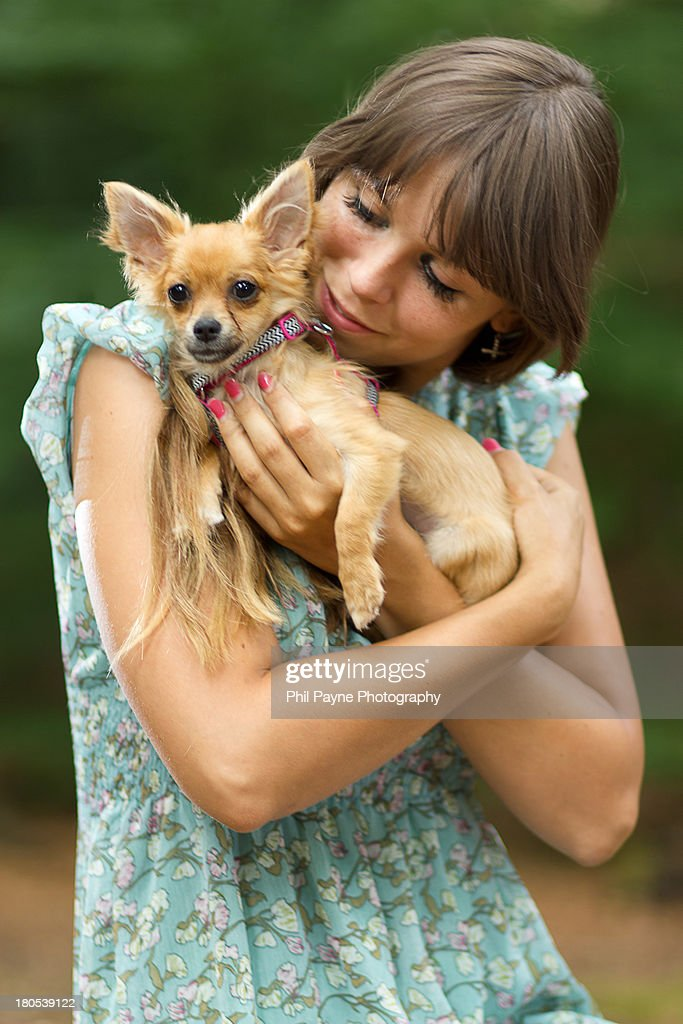Young woman holding small dog : Stock Photo