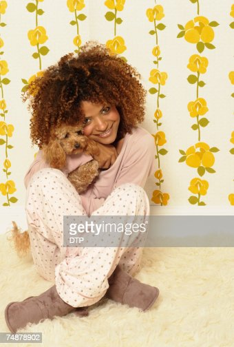 Young woman holding small dog, smiling, portrait : Stock Photo