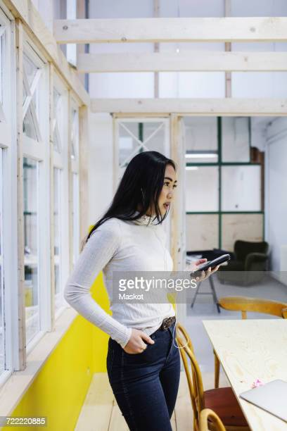 Young woman holding smart phone while standing in creative office
