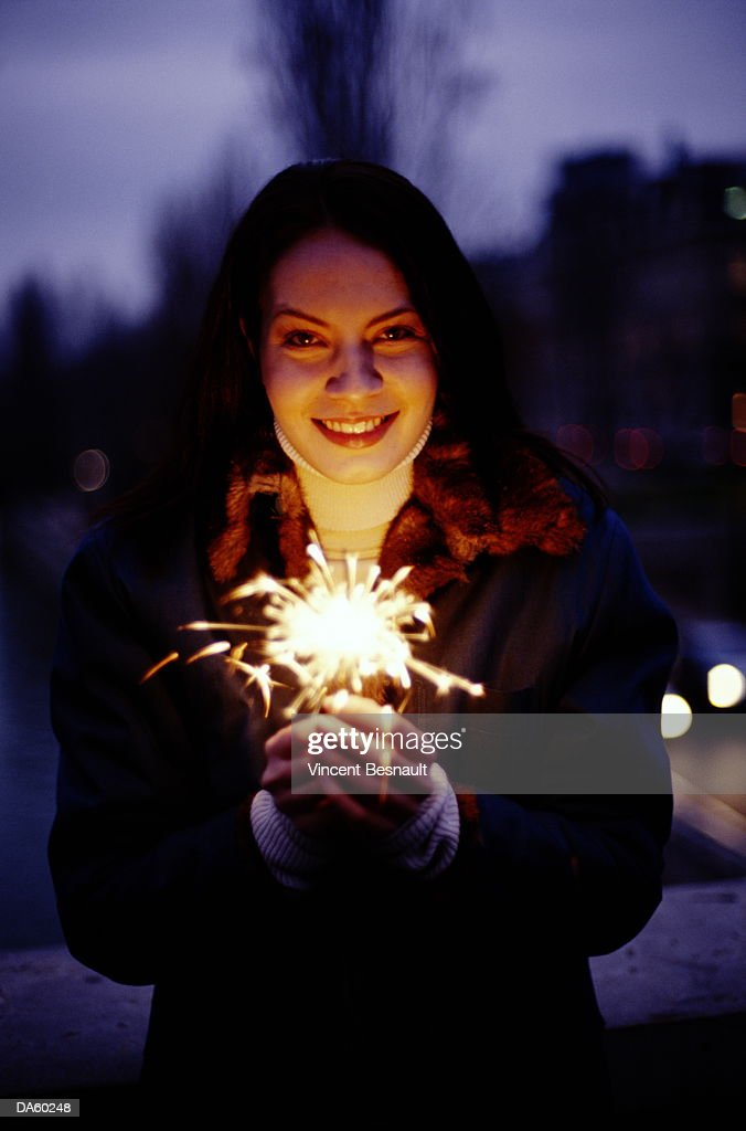 Young woman holding sparkler, outdoors at night : Stock Photo