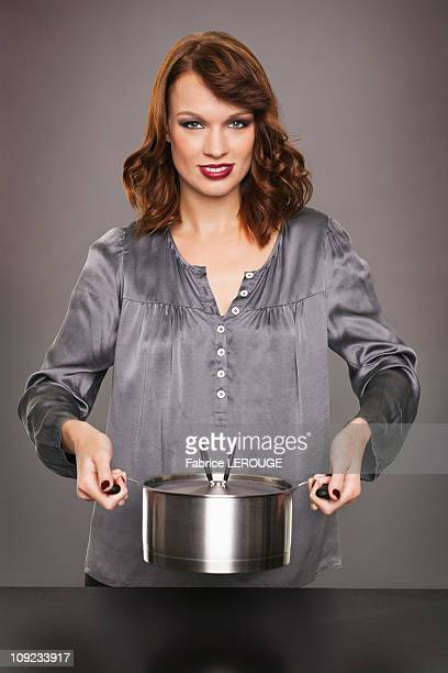 Young woman holding stew pot