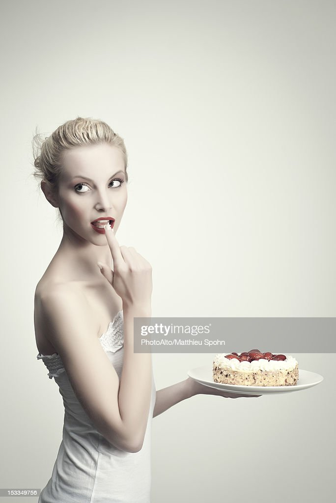 Young woman holding strawberry cake, licking cream off finger, portrait : Stock Photo