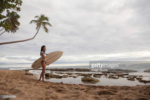 Young woman holding surfboard, portrait