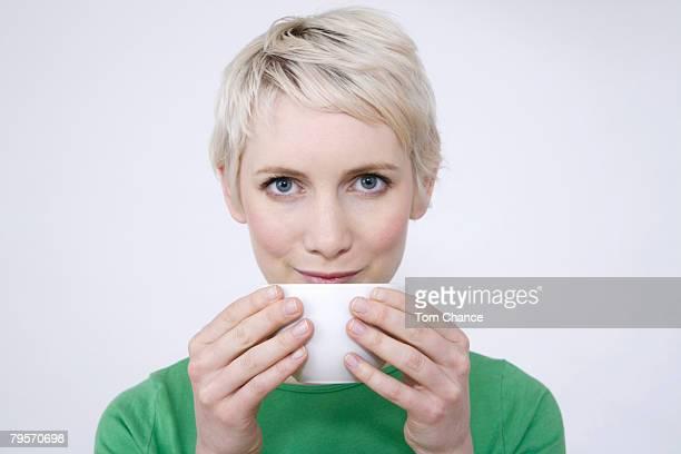 'Young woman holding tea bowl, portrait'