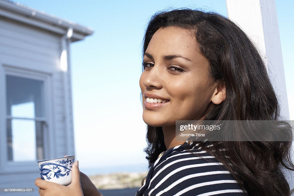 Young woman holding  tea cup, smiling : Stock Photo