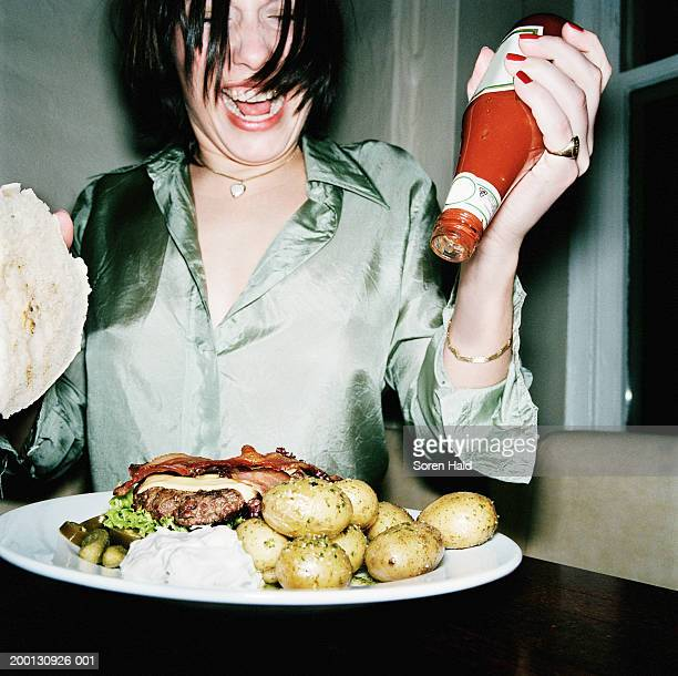 Young woman holding tomato sauce bottle over plate of food