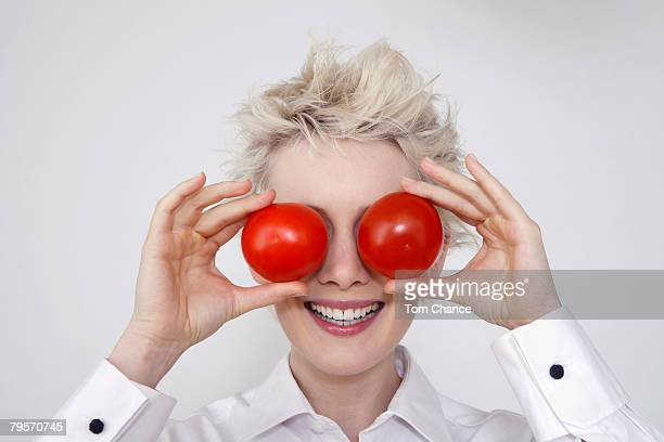 'Young woman holding tomatoes in front of her eyes, portrait'