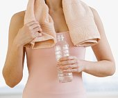 Young woman holding towel and water bottle
