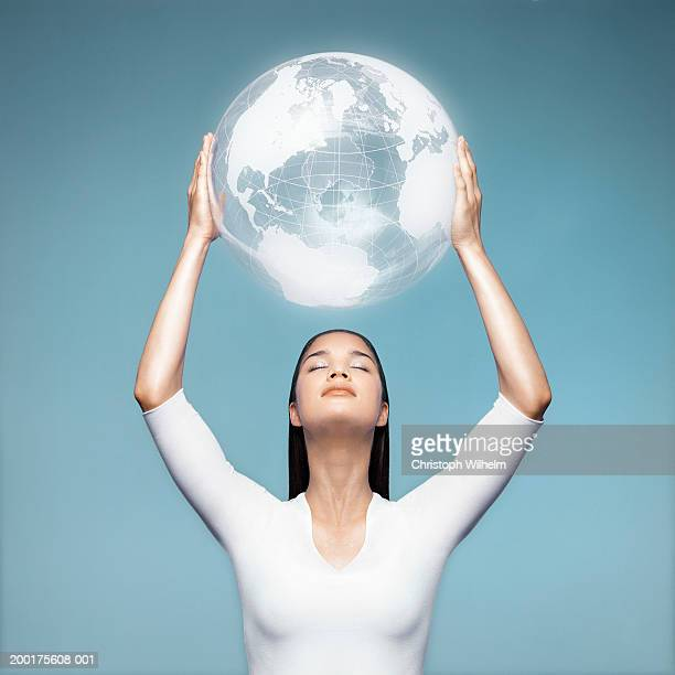 Young woman holding transparent globe above head