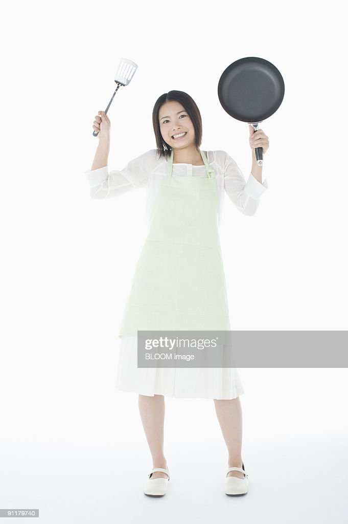 Young woman holding turner and frying pan, studio shot
