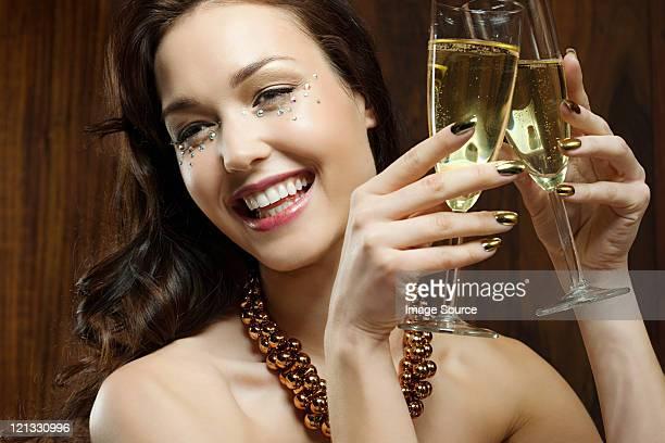 Junge Frau hält zwei Champagner-Flöten