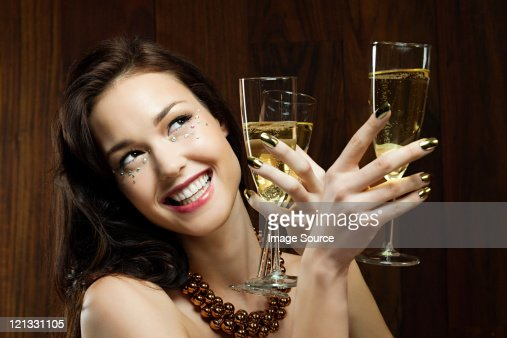 Young woman holding two champagne flutes : Stock Photo