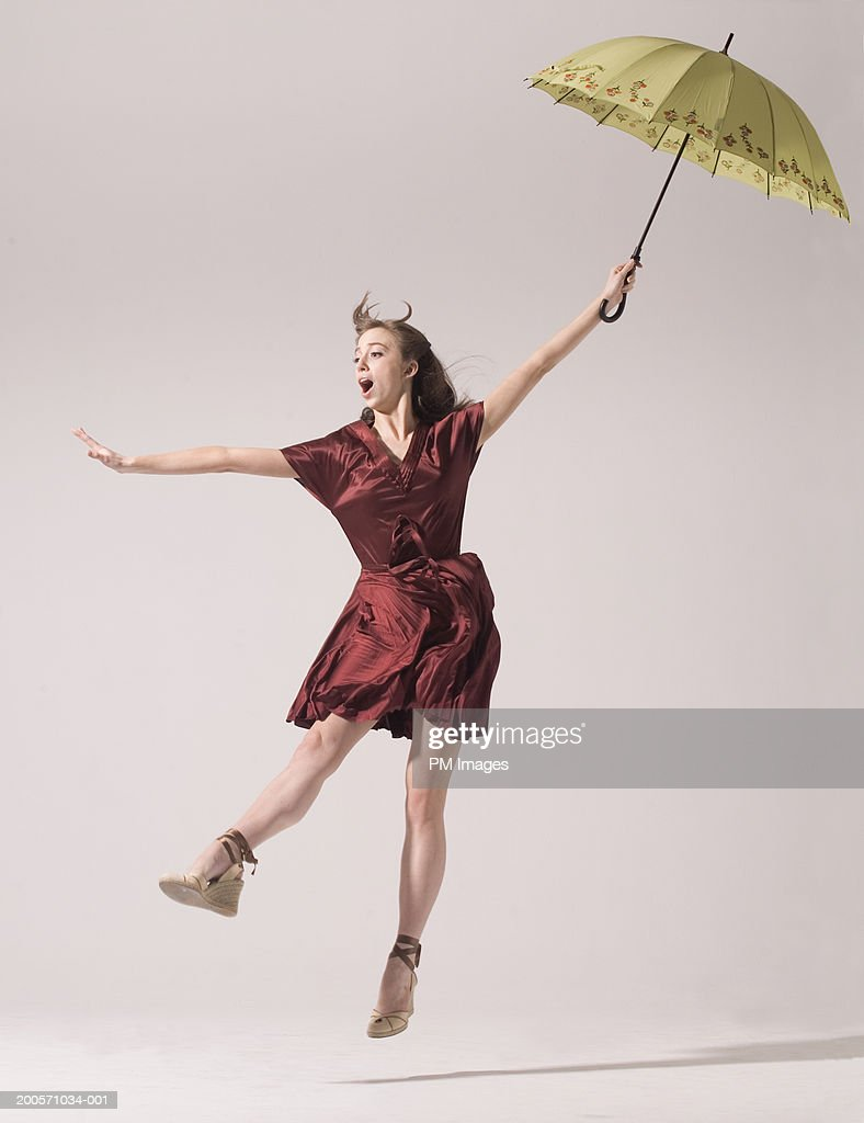 Young woman holding umbrella and blowing in wind