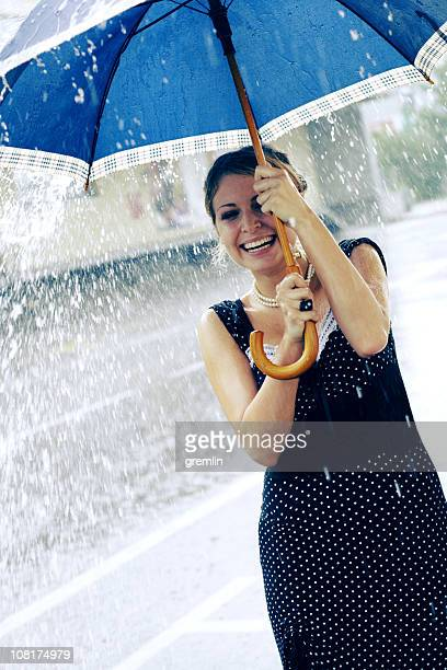 Young Woman Holding Umbrella During Rain Fall