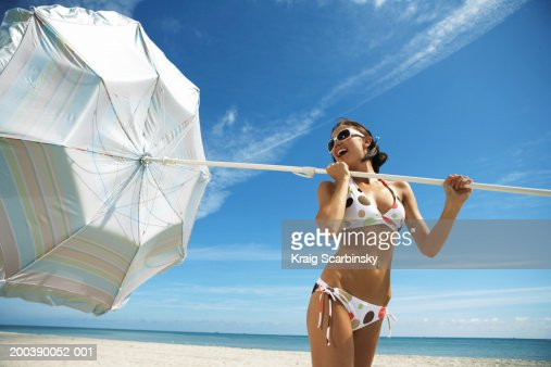 Young woman holding umbrella on beach, looking back, close-up