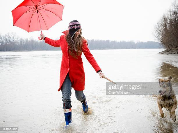 Young woman holding umbrella, running in river with dog, smiling