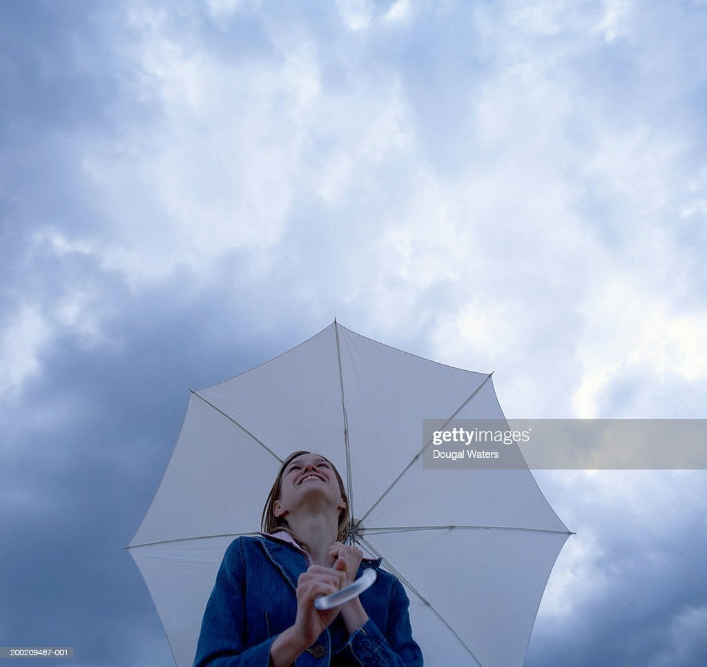 Young woman holding umbrella, smiling, low angle view : Stock Photo
