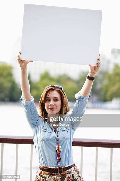 Young woman holding up a white board