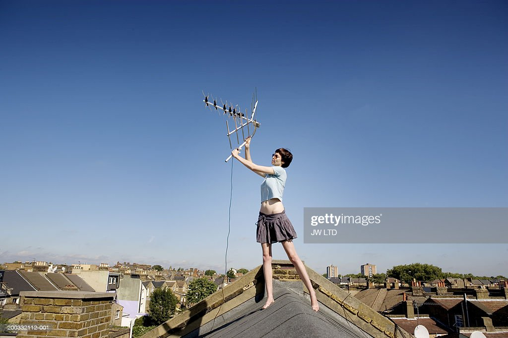 Young woman holding up aerial on rooftop