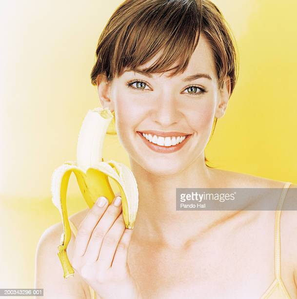 Young woman holding up banana, smiling, portrait, close-up