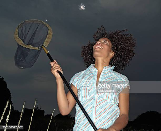Young woman holding up butterfly net towards floating seeds