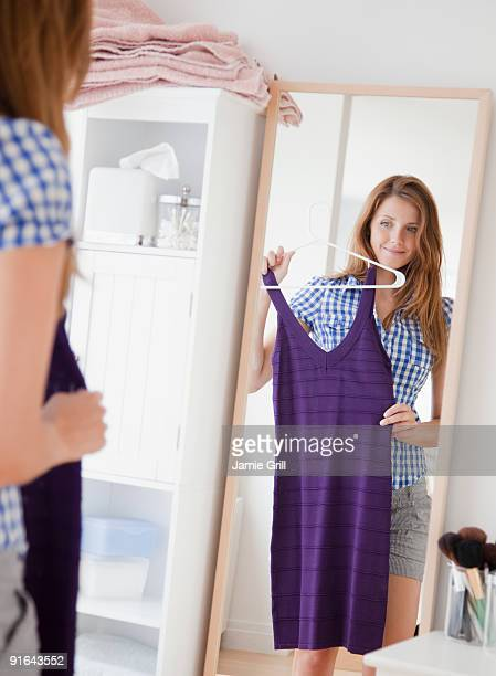 Young woman holding up dress in front of mirror