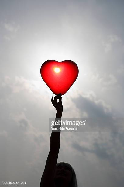 Young woman holding up heart shaped balloon
