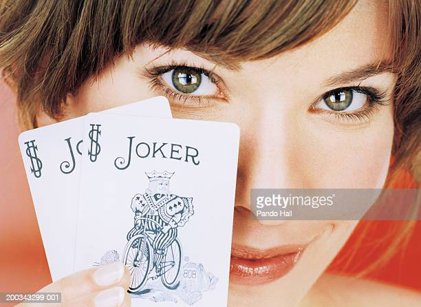 Young woman holding up joker playing card, smiling, portrait, close-up