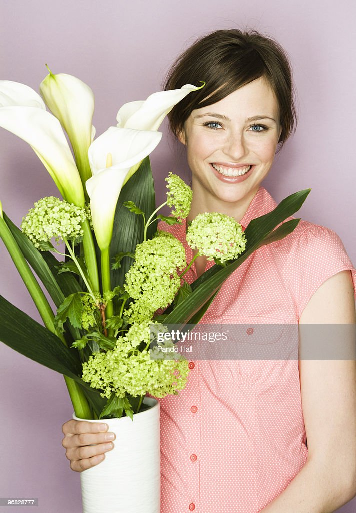 Young Woman Holding Vase With Flowers Smiling Stock Photo ...