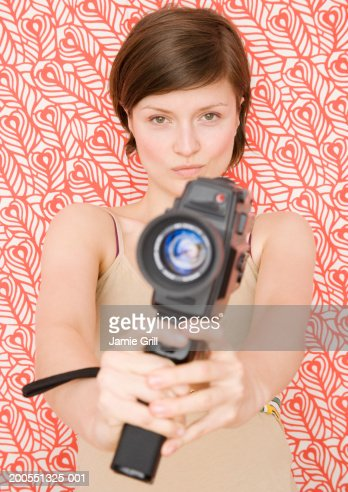 Young woman holding video camera, close-up, portrait : Stock Photo