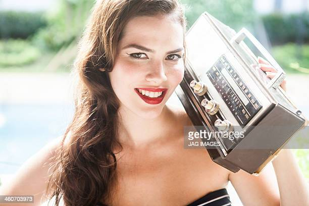 Young woman holding vintage radio