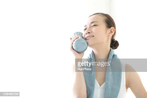young woman holding water bottle to face : Stock Photo