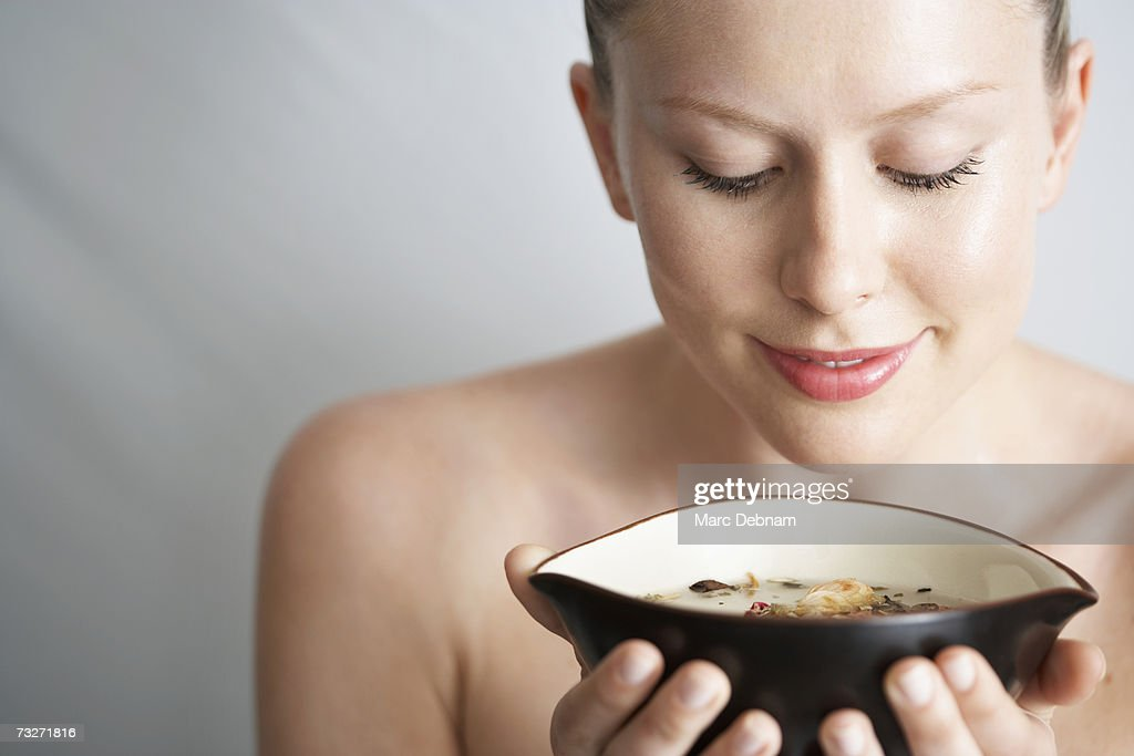 Young woman holding water bowl, close-up : Stock Photo