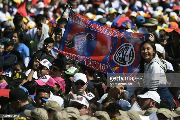 A young woman holds a flag of Argentina's San Lorenzo soccer team as people gather to see Pope Francis as he delivers a speech from a balcony of the...