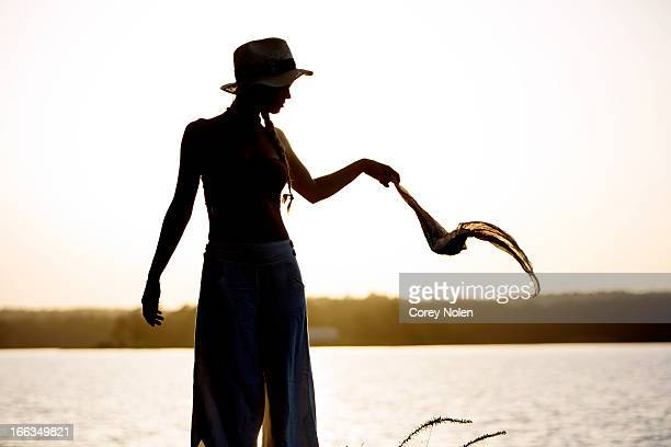 A young woman holds a scarf in the wind on the shore of Lake Martin, Alabama.