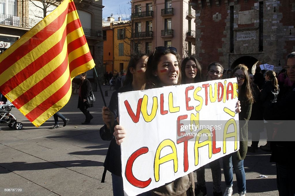 A young woman holds a sign reading 'I want to study in Catalan' during a demonstration in Perpignan on February 6, 2016 against proposed school reforms. About 300 people participated in the demonstration against school reforms, which they believe will lead to a reduction in the hours of Catalan teaching. / AFP / RAYMOND ROIG