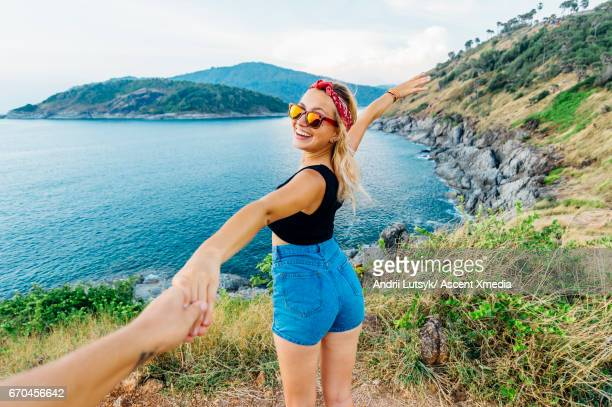 Young woman holds hands out, on hillside above sea