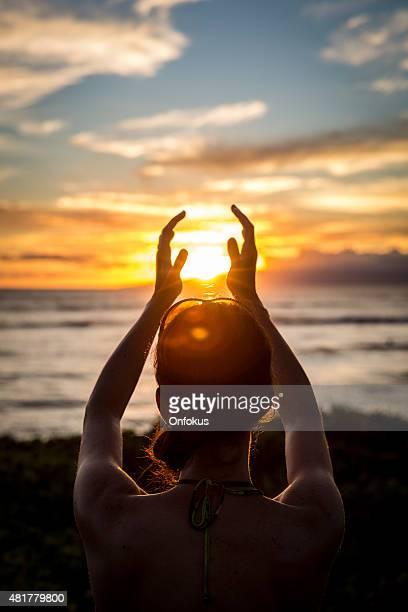 Jeune femme détient le soleil dans ses mains au coucher du soleil