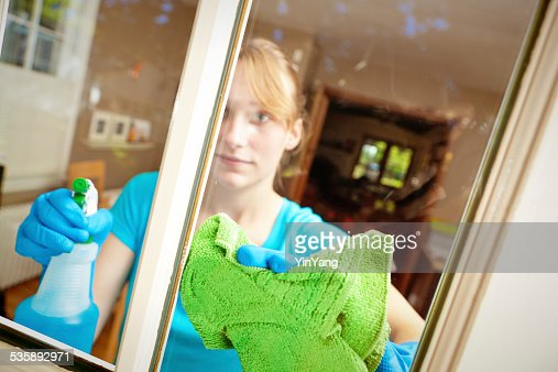 Young Woman Homemaker Spring Cleaning Home Window Glass with Sprayer : Stock Photo